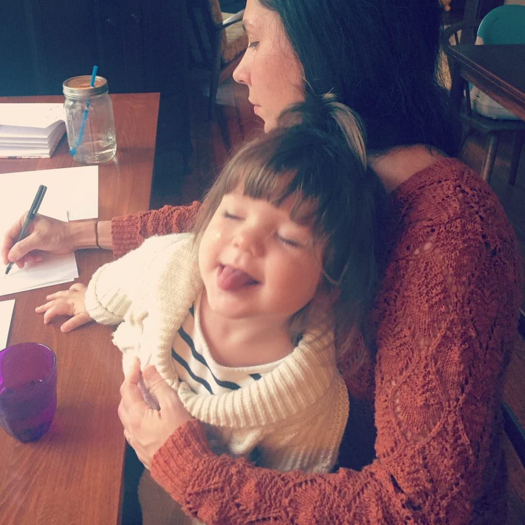 Photo of Marsha holding her young daughter while writing